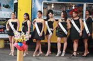 2009, Lawrence, MA. Candidatas al concurso Miss Peinado se preparan a desfilar.<br /> <br /> Esta imagen es interesante por que resume una mezcla de elementos dispares. Lo primero, es que el setting del concurso de belleza es un parking lot. Segundo, el fondo, background del evento es una casilla de venta de chimi-churis y fritura. Lo tercero a rese&ntilde;ar es lo primero que se nota: Las 7 candidatas -todas a exception de una- luce estar en un mundo propio, como si estuvieran cada una sintonizando y oyendo su propia emisora.<br /> <br /> Mientras el fot&oacute;grafo justo en frente, hace esfuerzos desesperados en procurar de concentrar la atenci&oacute;n de las 7. <br /> <br /> Otro elemento es el ingenioso arreglo floral que cubre la parte alta del poste amarillo de seguridad y como contrasta con las hermosas piernas y calzados detr&aacute;s. <br /> English: English translation available upon request