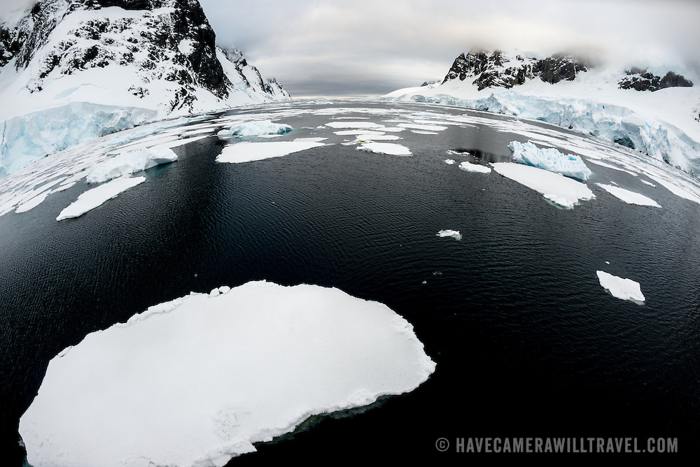 Plates of sea ice cover some of the water fo the Lemaire Channel, while scenic mountains tower along the shoreline.