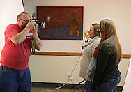 Eric Benson of Eric Benson Photography in Cedar Falls (from left) takes a picture of Vala Calkins-Kindon and her daughter, Samantha Kindon, both of Iowa City, during the second annual Help-Portrait Iowa City at the Iowa Memorial Union in Iowa City on December 7, 2013. Help-Portrait Iowa City provides free portraits to individuals, couples, and families. Participants have the option to start with a hairstylist and make-up artist and leave with a printed and framed photograph.