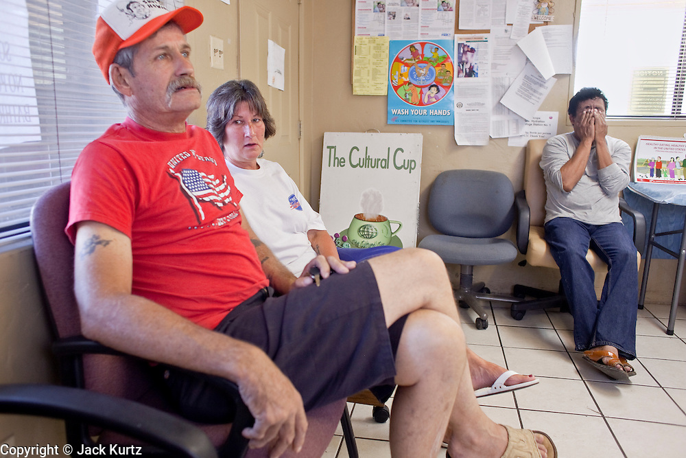 13 JUNE 2009 - PHOENIX, AZ: Ron Baker, left, waits with his girlfriend, Tanya Gardino, for Gardino to see a doctor at the Cultural Cup walk in clinic about shoulder pain. Gardino, who has no health insurance, was referred to the clinic by a Phoenix social service agency. The walk in clinic at the Cultural Cup Food Bank started two years ago when Cultural Cup founder Zarinah Awad wanted to expand the food bank's outreach and provide basic medical care for the people who use the food bank. The clinic sees, on average, 7 - 11 patients a week. Awad said that as the economy has worsened since the clinic opened and demand has steadily increased. She attributes the growth to people losing their jobs and health insurance. The clinic is staffed by volunteers both in the office and medical staff. Adults are seen every Saturday. Children are seen one Saturday a month, when a pediatrician comes in. Awad, a Moslem, said the food bank and clinic are rooted in the Moslem tradition of Zakat or Alms Giving, the giving of a small percentage of one's income to charity which is one of the Five Pillars of Islam.   PHOTO BY JACK KURTZ