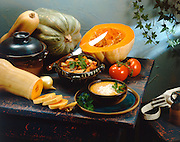 Still life with pumpkin soup, gourds and squash