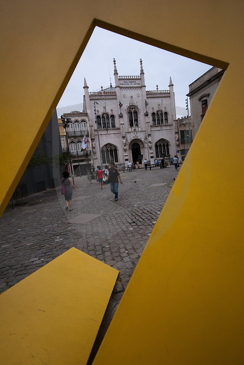 yellow abstract planar sculpture framing the neo-manuelian architecture of the real gabinete portugues de leitura building in downtown rio de janeiro, brazil.