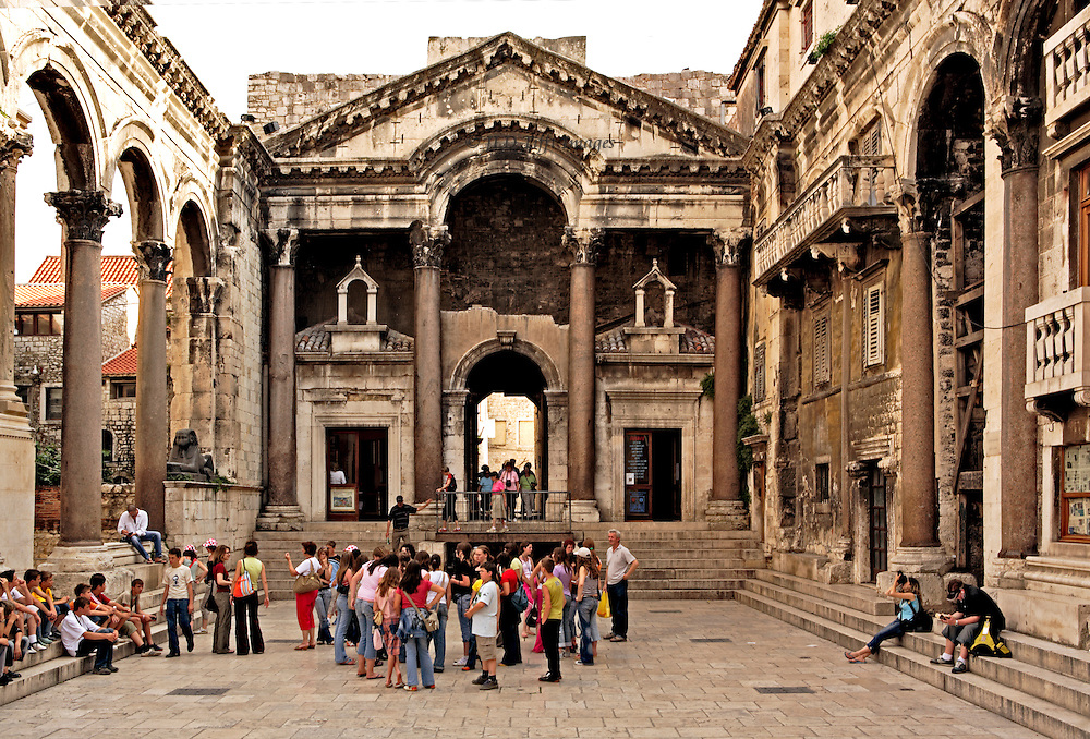 Split, Diocletian's Palace, groups of tourists standing about, seated on the steps. View of the peristyle looking toward the entrance to the palace residential area.