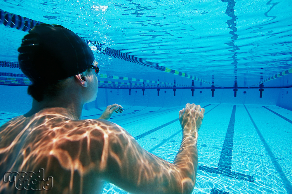 Male swimmer wearing United States swimming cap in pool