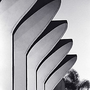 Vertical, black and white shot of curved building facades.