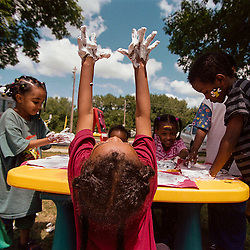 In a joyous stretch, Roqoya Abdi shows her foamed hands to the skies while participating in the Summer Neighborhood Activity Program. The Summer of Service volunteers help with the program that visits different  area neighborhoods twice weekly.
