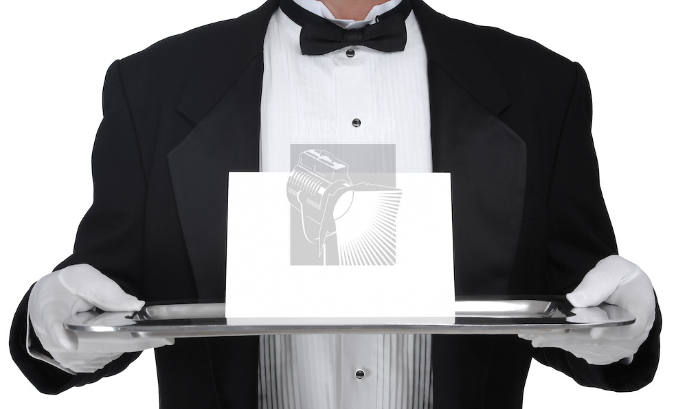 Butler in tuxedo presenting a blank card on a silver tray