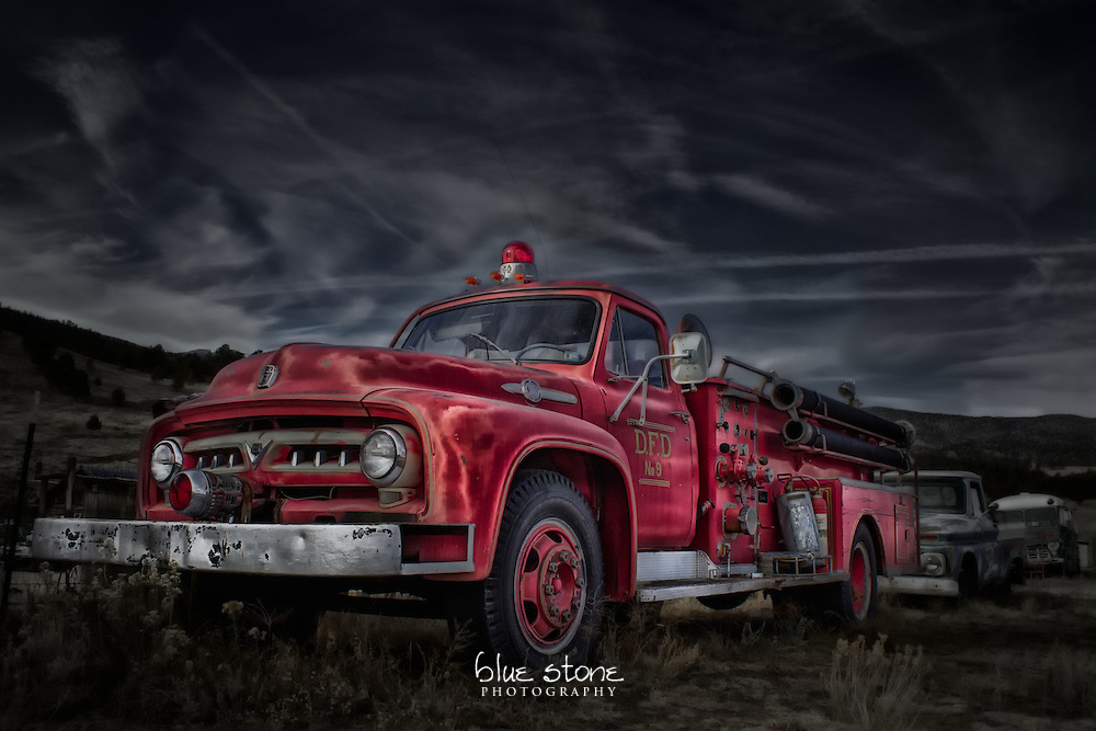 A photograph of a historic vintage red fire truck is processed with a blend of realism and artistic style creating a misleading composition.<br />