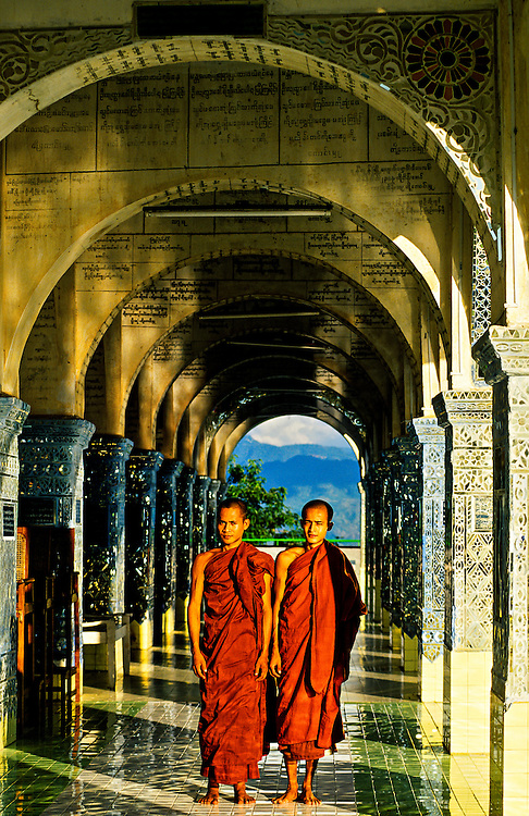 Monks walking through the aches at Sutaungpyi Pagoda on top of Mandalay Hill, Mandalay, Burma (Myanmar)