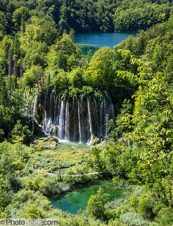 Multiple streams of the beautiful waterfall Veliki prstavac plunge 28 meters. Plitvice Lakes National Park (Nacionalni park Plitvicka jezera, in Croatia, Europe) was founded in 1949 and is honored by UNESCO as World Heritage Site. Waters flowing over limestone, dolomite, and chalk in this karstic landscape have, over thousands of years, deposited travertine barriers, creating natural dams, beautiful emerald lakes and waterfalls. Warming conditions after the last Ice Age (less than 12,000 years ago) allowed the natural dams to form from tufa (calcium carbonate) and chalk depositing in layers, bound by plants. Plitvicka Jezera is a municipality of Lika-Senj County, in the Republic of Croatia.