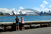 Two children (10 years old, 6 years old) looking across water to Sydney Opera House. Sydney, Australia