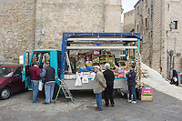 GANGI, ITALY - 30 MAY 2015: A fruit vendor sells fruit and vegetable on a truck at the entrance of Gangi, Italy, on May 30th 2015. Gangi is a town with a population of 7,000 between Palermo and Catania, in the centre of Sicily, whose local administration is giving away abandoned houses of the historical centre for free. The Mayor of Gangi Giuseppe Ferrarello conceived the initiative of giving houses for free as a means to diversify the local economy - primarily dependent on agriculture and animal husbandry - by boosting tourism-related activities, and consequently counteract the phenomenon of depopulation that is typical of many small Italian towns where employment possibilities have been on a downward trajectory for years. The renovations of the assigned homes have also given work to local artisans.