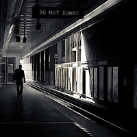 "A silhouetted man walking through a train station with a ""DO NOT BOARD"" sign overhead."