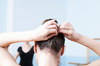 Young woman adjusts hair during ballet class
