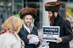 © Licensed to London News Pictures. 26/09/2018. Liverpool, UK. Orthodox Jews distribute leaflets and hold a sign which reads 'Jeremy Corbyn is a Friend of the Jews' outside the Labour Party Conference ahead of Labour Leader Jeremy Corbyn's speech. Photo credit: Rob Pinney/LNP