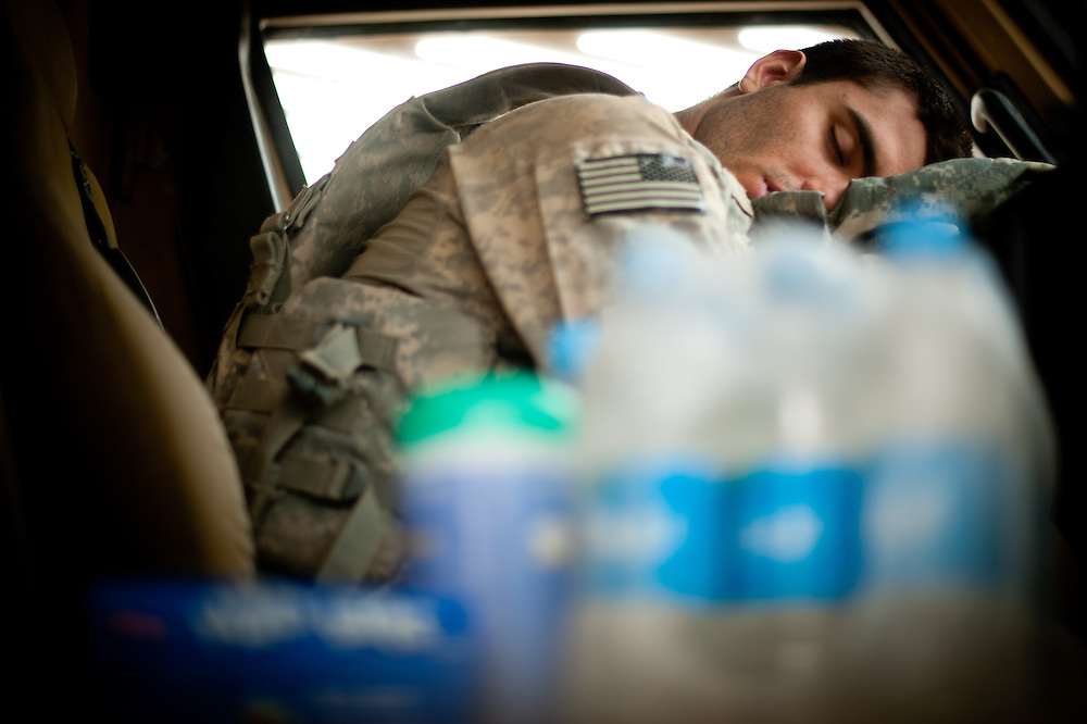 A soldier sleeps in the cab of a Mine-Resistant Ambush-Protected vehicle (MRAP).