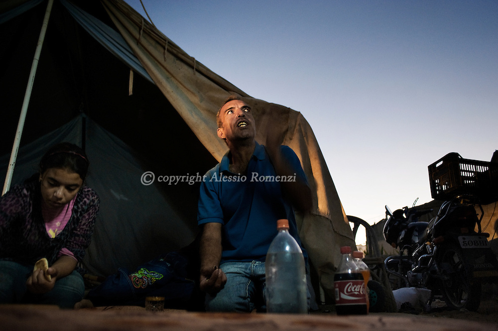 Kamal Abu Rabih eats in front of one of the tents where he lives with his family of eight before an iftar meal in the northern Gaza Strip town of Beit Lahia September 9, 2010, on the eve of the Eid Al-Fitr holiday which marks the end of the fasting month of Ramadan. After being displaced during the 2009 Israeli offensive on the Gaza Strip where they lost a son, Abu Rabih's family of eight moved into tents in Beit Lahia from where they are currently under threat of eviction by the local municipality.© ALESSIO ROMENZI