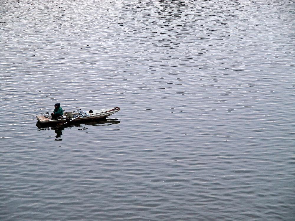 Fisherman on Vltava river under Charles  Bridge in the city center of Prague.