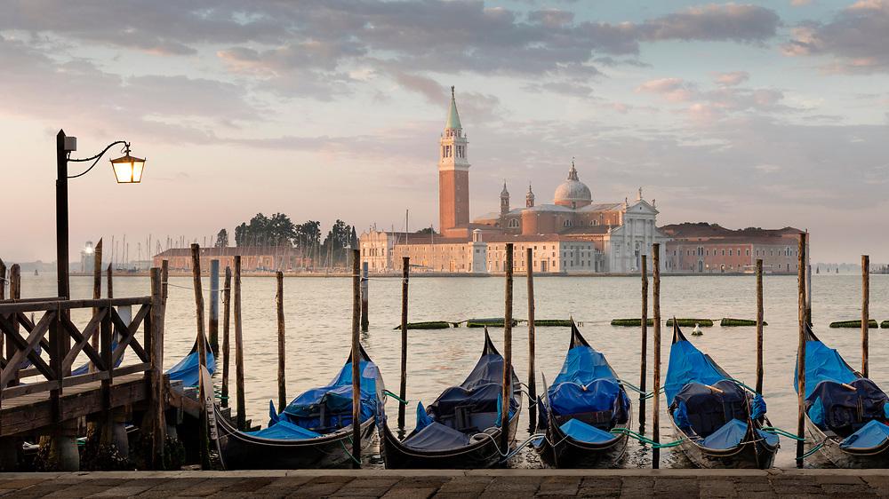 Vertäute Gondeln in Venedig mit Blick Richtung der Insel San Giorgio Maggiore bei Sonnenaufgang.