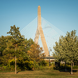 Boston Leonard Zakim Bunker Hill Bridge photo with park trees. The Leonard P. Zakim Bunker Hill Memorial Bridge is a cable bridge that spans the Charles River in Boston, Massachusetts in the Eastern United States of America.