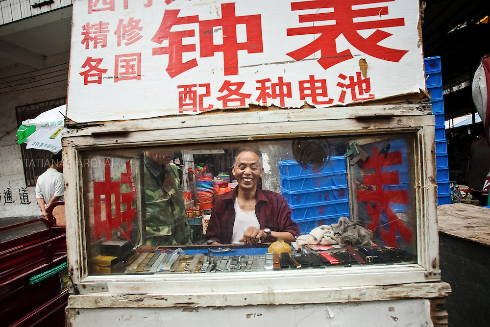 A clockmaker works in the street of Guilin city, Guangxi Province of China.