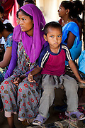 Lakshmi Tharu (in purple), 22, sits with her younger of 2 sons aged 10 and 4 as she gathers with other child mothers and child brides to see Pahari Tharu, 52, the female community health worker in Bhaishahi village, Bardia, Western Nepal, on 29th June 2012. Lakshmi has never been to school and was married to an 11 year old boy when she was nine, giving birth to her first child when she was 12. In Bardia, StC works with the district health office to build the capacity of female community health workers who are on the frontline of health service provision like ante-natal and post-natal care, and working together against child marriage and teenage pregnancy especially in rural areas. Photo by Suzanne Lee for Save The Children UK