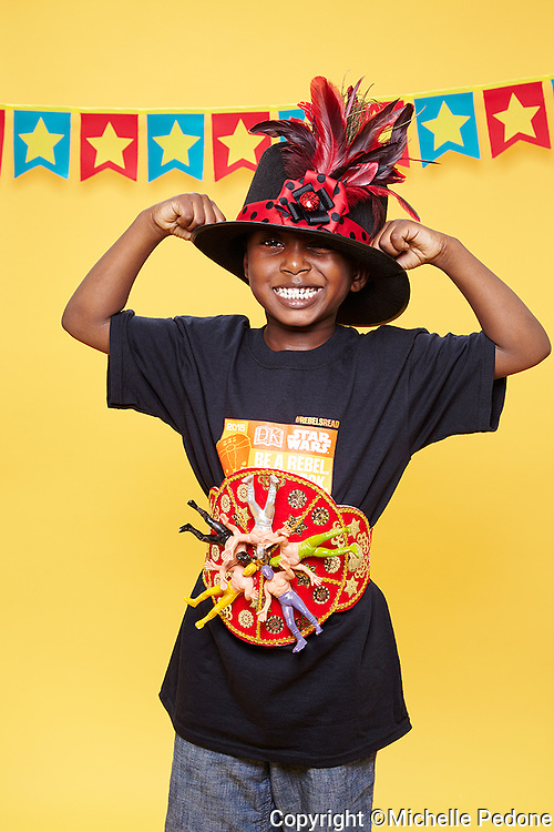 Emmanuel wearing a black and red feathered hat striking a wrestling pose<br /> Shot at Photoville Photo Booth, September 20, 2015
