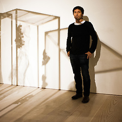 London, UK - 2 September 2014: Artist Xavier Mascaró poses next to the shadow of his works 'Masks'. Xavier Mascaró's first UK solo exhibition will run from 3 September until 5 October at Saatchi Gallery.