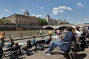 People sitting at an outdoor cafe watching runners on the newly renovated pedestrianised section of the Voie Georges Pompidou, a West-East roadway across Paris, on the Quai des Gesvres on the right bank of the river Seine, in the 4th arrondissement of Paris, France. Behind is the Pont au Change, the Greffe du Tribunal de commerce de Paris and the Conciergerie, on the Ile de la Cite. Picture by Manuel Cohen