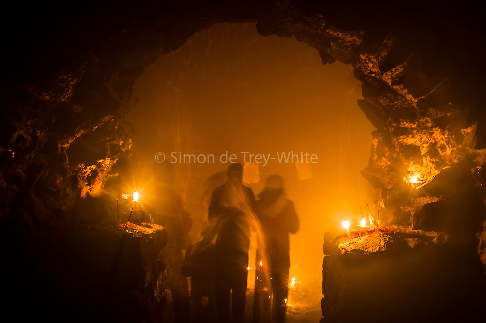 27th November 2014, New Delhi, India. People pray, light candles, incense sticks and ask for wishes to be granted by Djinns in the ruins of Feroz Shah Kotla in New Delhi, India on the 27th November 2014<br /> <br /> PHOTOGRAPH BY AND COPYRIGHT OF SIMON DE TREY-WHITE a photographer in delhi<br /> + 91 98103 99809. Email: simon@simondetreywhite.com<br /> <br /> People have been coming to Firoz Shah Kotla to leave written notes and offerings for Djinns in the hopes of getting wishes granted since the late 1970's. <br /> Feroz Shah Tughlaq (r. 1351&ndash;88), the Sultan of Delhi, established the fortified city of Ferozabad in 1354, as the new capital of the Delhi Sultanate, and included in it the site of the present Feroz Shah Kotla. Kotla literally means fortress or citadel. The pillar, also called obelisk or Lat is an Ashoka Column, attributed to Mauryan ruler Ashoka. The 13.1 metres high column, made of polished sandstone and dating from the 3rd Century BC, was brought from Ambala in 14th century AD under orders of Feroz Shah. It was installed on a three-tiered arcaded pavilion near the congregational mosque, inside the Sultanate's fort. In centuries that followed, much of the structure and buildings near it were destroyed as subsequent rulers dismantled them and reused the spolia as building materials.