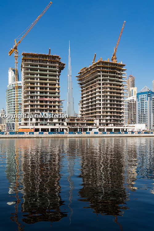 daytime view of construction of apartment towers and modern skyline of Business Bay in Dubai, United Arab Emirates