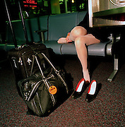 A female crew member rests tired feet while making a call in the airport terminal at Chicago-O'Hare airport, Illinois, USA.