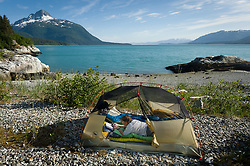 A kayaker writes in her journal in a tent on a beach near the Klotz Hills and not far from Maquinna Cove in Muir Inlet in Glacier Bay National Park and Preserve in southeast Alaska. Prominent in the background is Mt. Wright which is located at the mouth of Adams Inlet.