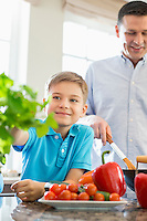 Smiling boy touching houseplant with father preparing food in kitchen