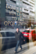 """A pedestrian walks pass a Barclays Bank sign saying """"where some see crisis I see opportunity"""" in Bilbao, Spain."""