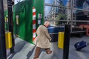 An elderly gentleman passes by, next to a construction hoarding for a future office building.