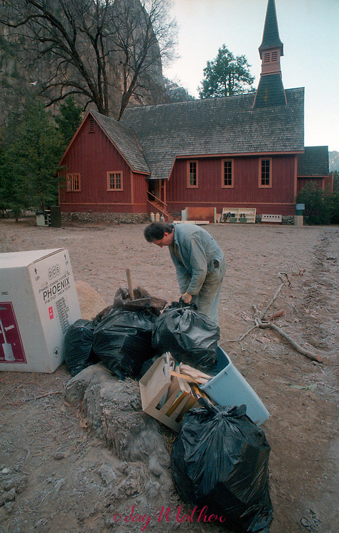 Brian Emple, pastor of the Yosemite Community Church removes a bag of debris from the church after flood waters receded.  The foundation of the building was raised three feet after a flood in 1964.  The 1997 flood came into the church with more than three additional feet of water.  January 1997