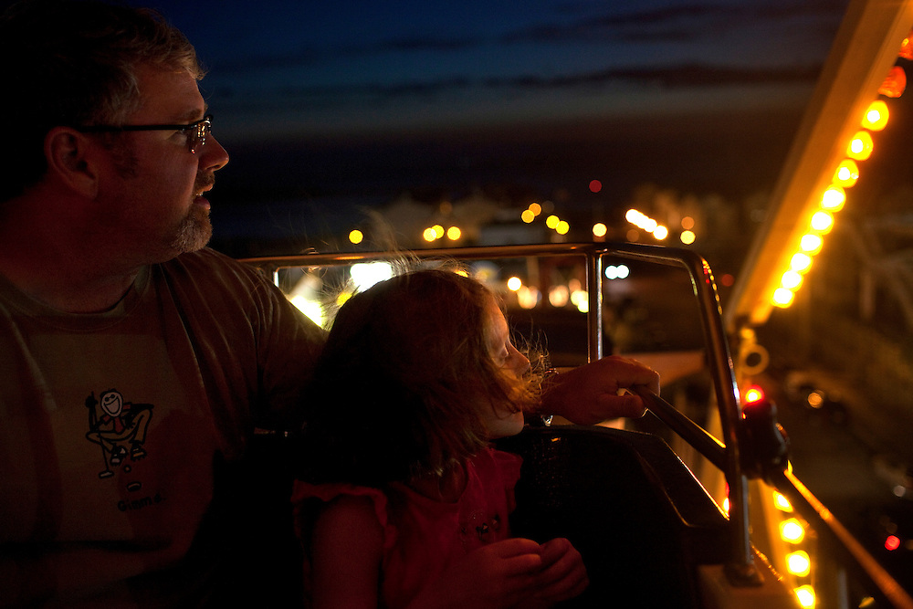 Long Beach Island, NJ - June 29, 2013 :  Drew Coughlin with his daughter Gemma Coughlin, 6, from Glenrock, NJ, watch the end of the sunset at the top of the Ferris Wheel at Fantasy Island Amusement Park in Beach Haven on Long Beach Island, NJ on June 29, 2013. People are returning to the beaches for the summer after recovery efforts post Superstorm Sandy.