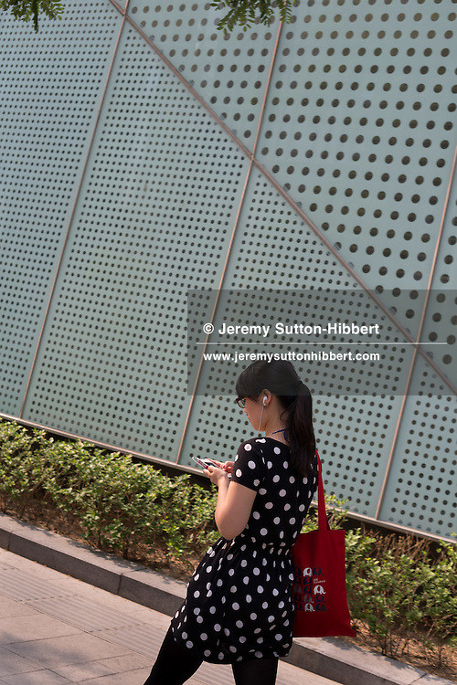 Girl in spotted dress, in front of spotted wall, in the business district, in Beijing, China, Thursday 7th June 2012.
