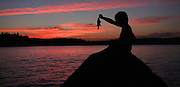 Photo by Gary Cosby Jr.  Ben Champagne sits on a rock to fish on Tupper Lake at sunset near the town of Tupper Lake, New York in Adirondack Park.