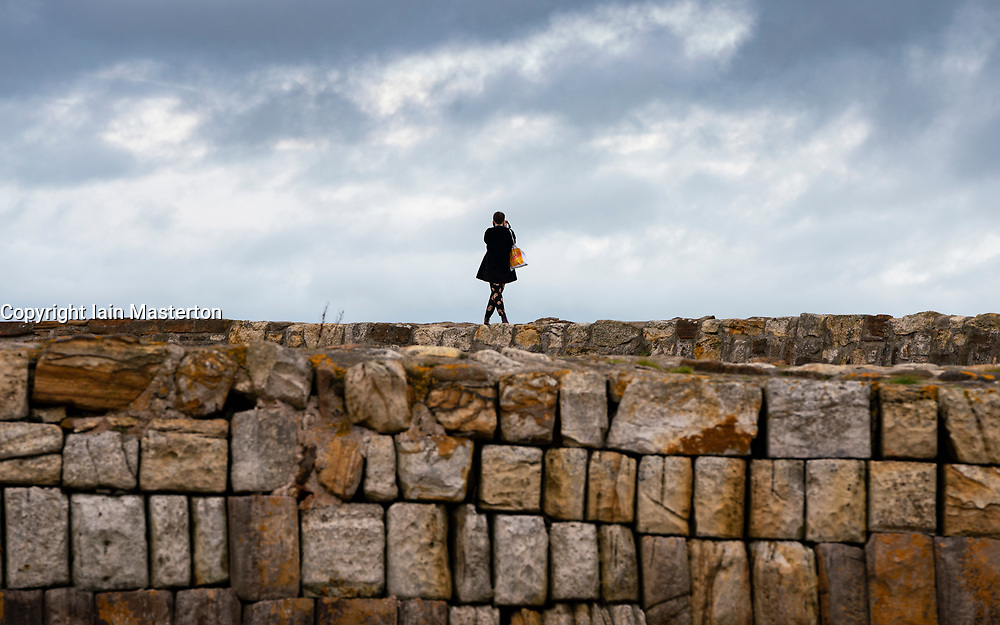 Solitary woman standing on harbour wall in St Andrews, Fife, Scotland, UK