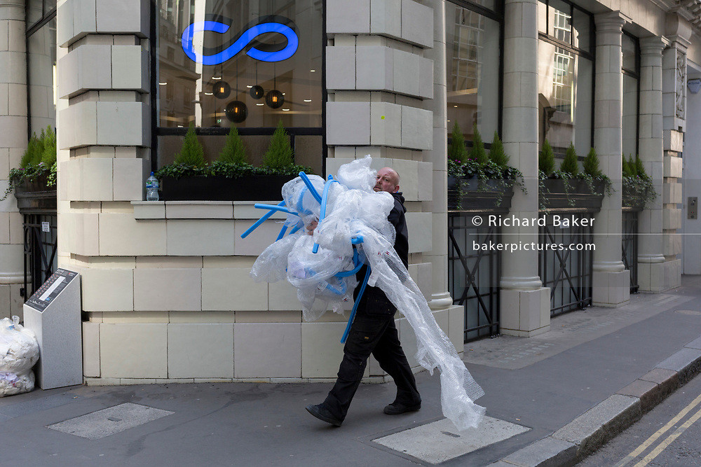 A workman struggles to carry packaging (including bubble wrap) in the City of London, the capital's financial district also known as the Square Mile, on 6th April 2017, in London, England.