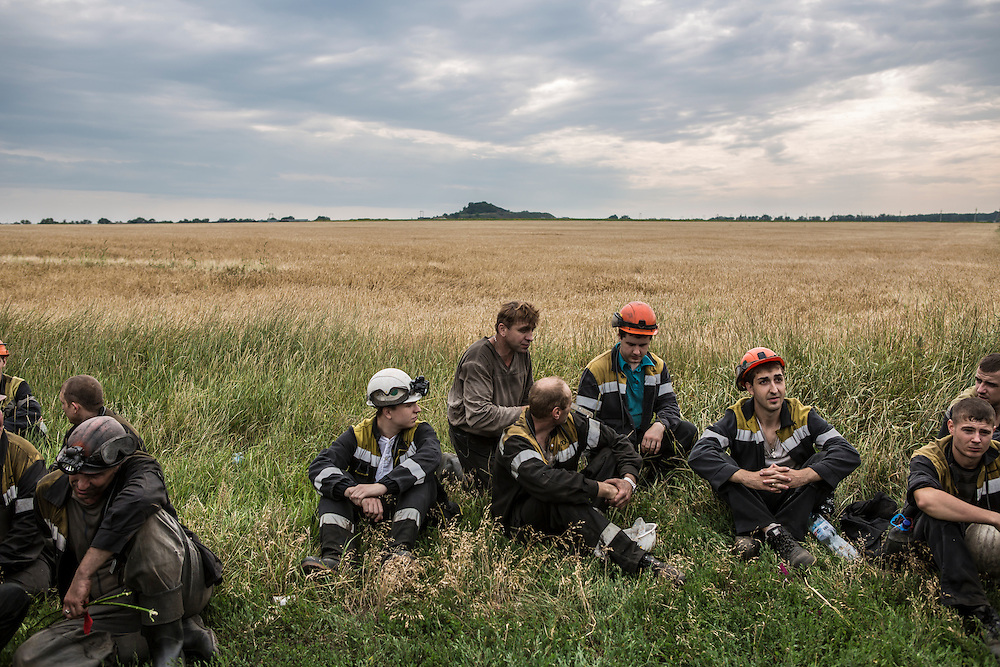 GRABOVO, UKRAINE - JULY 19: A group of coal miners takes a break after searching fields looking for remnants of Malaysia Airlines flight MH 17 on July 19, 2014 in Grabovo, Ukraine. Malaysia Airlines flight MH17 was travelling from Amsterdam to Kuala Lumpur when it crashed killing all 298 on board including 80 children. The aircraft was allegedly shot down by a missile and investigations continue over the perpetrators of the attack. (Photo by Brendan Hoffman/Getty Images) *** Local Caption ***