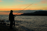 Angler fishing in the last light of evening at Kimmeridge Bay, Dorset