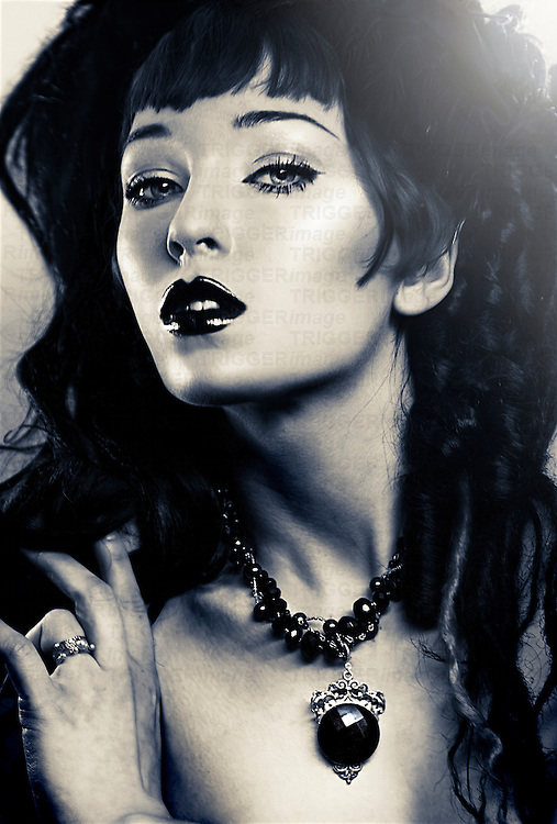 Duo-toned image of a young woman wearing beaded black cameo necklace looking directly at viewer