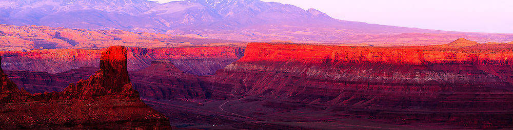 Warm light from the setting sun highlights canyon rims overlooking the Colorado River near Moab, Utah. The La Sal Mountains are visible in the background.<br />