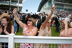 © Licensed to London News Pictures. 07/06/2014. Epsom, UK. Racegoers watch the horses cross the line at the first race, The Investec Out of the Ordinary Stakes.  Derby Day today 7th June 2014 at Epsom 2014 Investic Derby Festival in Surrey. Traditionally, elegant, fashionable racegoers gather for a classic day's racing at Epsom Racecourse, Surrey. Photo credit : Stephen Simpson/LNP