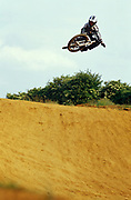 Mountain biker, Chico Hooke, in full protection getting some air on the track, UK, 2000's
