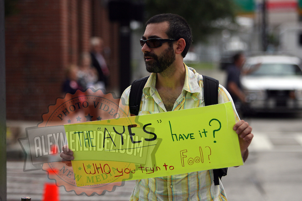 A protester holds a sign outside the RNC conference during the Republican National Convention in Tampa, Fla. on Wednesday, August 29, 2012. (AP Photo/Alex Menendez)