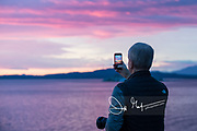A traveler aboard the National Geographic Quest uses a smartphone to take a photo of a pink sunset in British Columbia, Canada.
